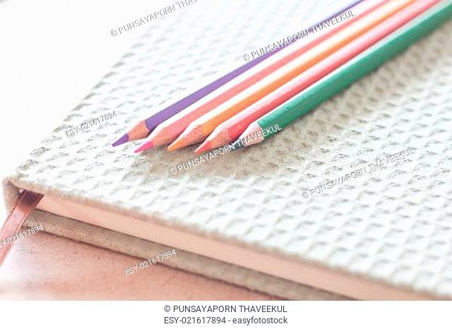 Closeup colorful pencils on green notebook