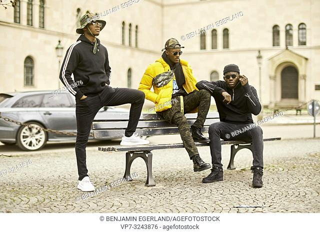 three urban male friends on bench at street in city, incidental car, in Munich, Germany
