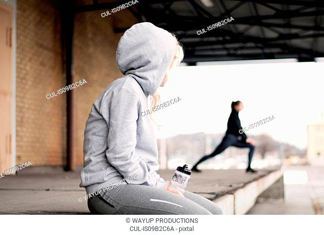 Female runner watching friend warming up outside warehouse