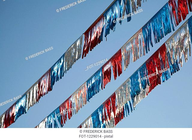 American flag coloured streamers against a clear blue sky