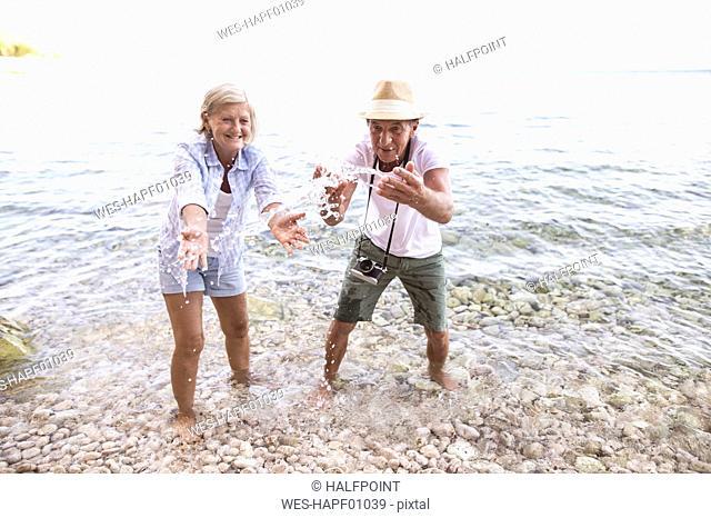 Senior couple splashing with water at seafront
