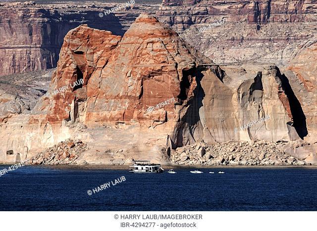 Red Navajo Sandstone cliffs at Lake Powell, houseboat in Wahweap Bay, Page, Arizona, USA