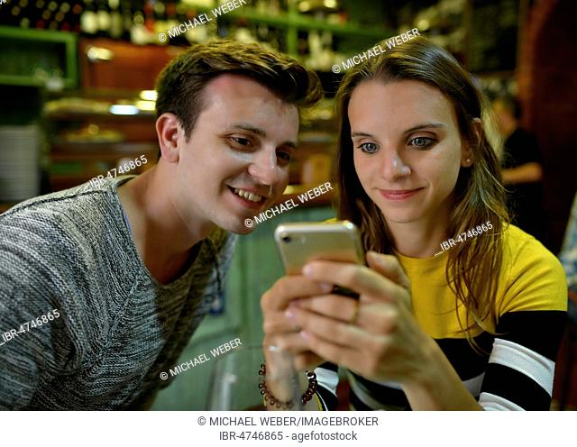 Young couple looks interested in mobile phones, Tenerife, Canary Islands, Spain