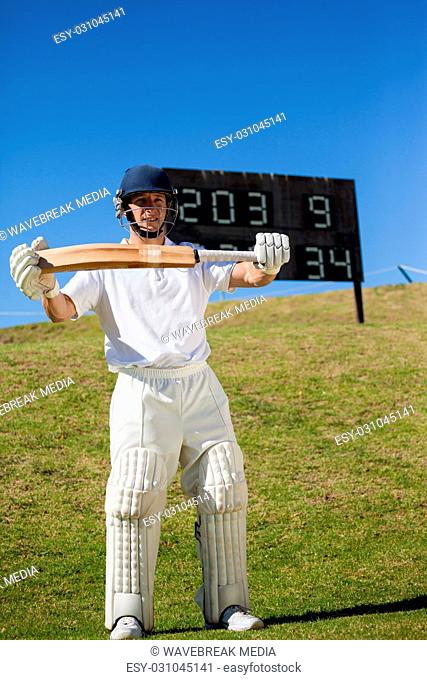 Confident cricketer with bat standing on field