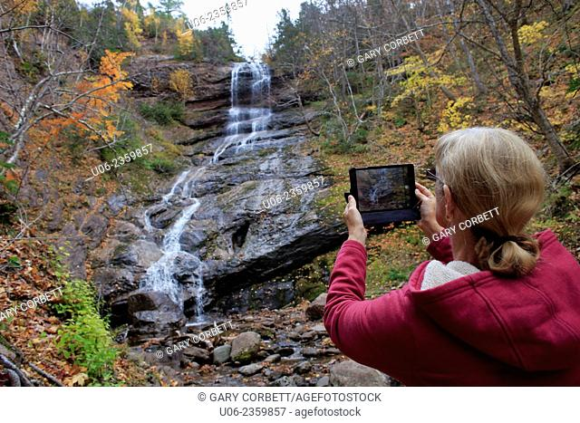 A woman taking a photo of a waterfall with an apple ipad