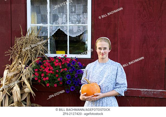 Wolcott Vermont Mennonite young girl aged 18 at home with pumpkin in fall colors in October and flowers in window