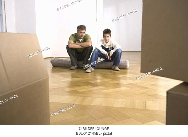 portrait of father and son sitting on carpet amongst moving boxes