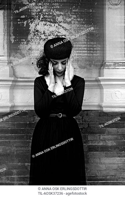 Young female adult wearing black clothing and veil standing in front of memorial