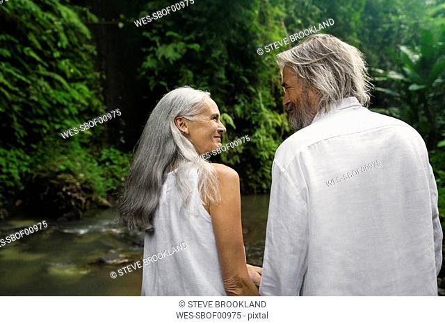 Handsome senior couple smiling at each other in tropical jungle