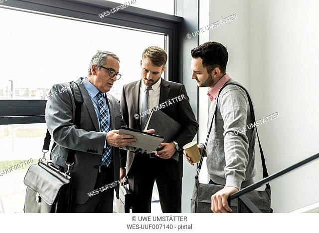 Three businessmen with digital tablet talking in staircase