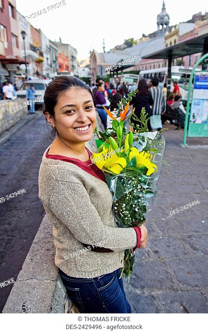 Young woman holding a bouquet of flowers in the street; Guanajuato, Mexico