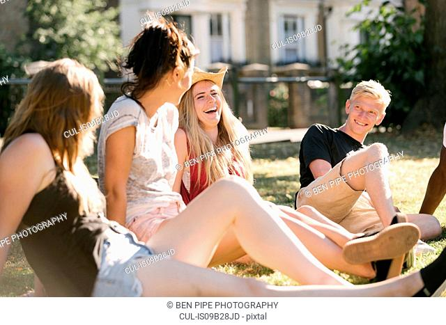 Young man and female friends chatting in park
