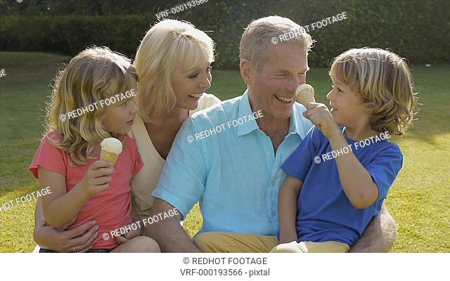 Grandparents and grandchildren sitting together in garden playing with ice cream