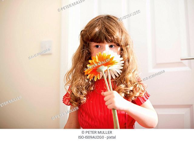 Portrait of cute girl smelling cut flowers