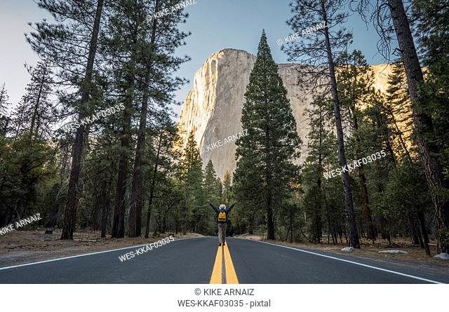 USA, California, Yosemite National Park, man with raised arms on road with El Capitan in background
