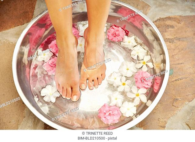 Caucasian woman soaking feet in tub with flowers