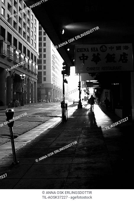 Bright sunlight in urban environment with street and high rise buildings seen from sidewalk with silhouetted figures