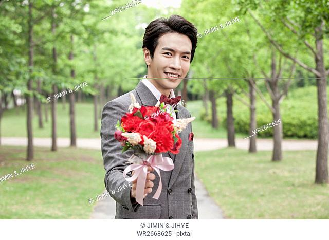 Portrait of young smiling groom holding flowers outdoors