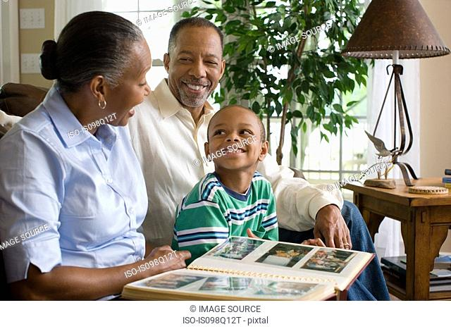 Grandparents and their grandson looking at a photo album
