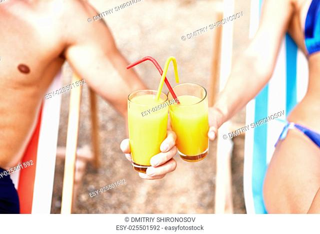 Glasses with fresh orange juice and straws held by couple