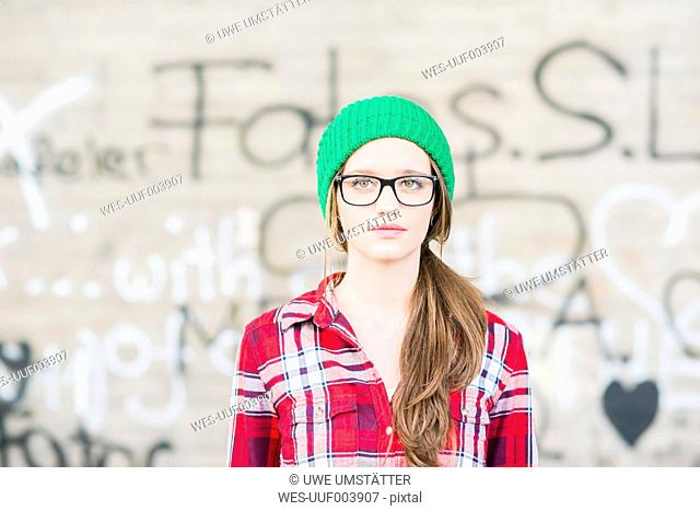 Young woman with checkered shirt and green wooly hat at graffiti wall