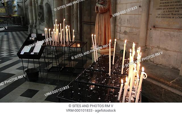 TILT up, PAN. Interior: South Choir Aisle, statue of St. Rita and lit candles. The Cathedral is in the High Gothic or Classical French style