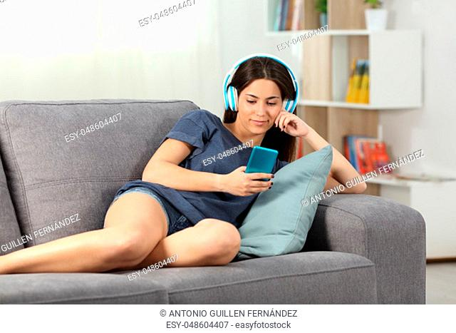 Relaxed teen listening to music lying on a couch in the living room at home