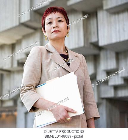 Serious Japanese businesswoman holding paperwork
