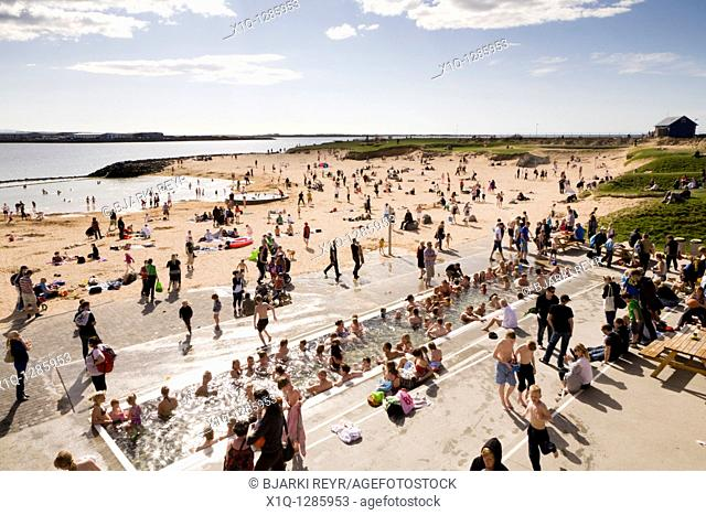 People enjoying the day at Nautholsvik beach, Reykjavik Iceland  The water in the lagoon is heated using geothermal water