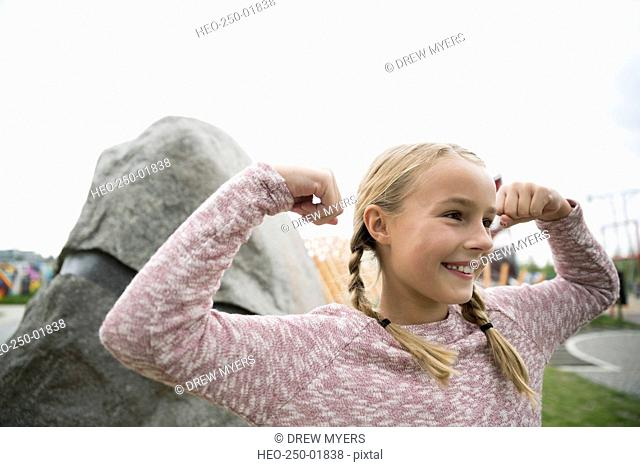 Portrait confident girl flexing muscles at playground