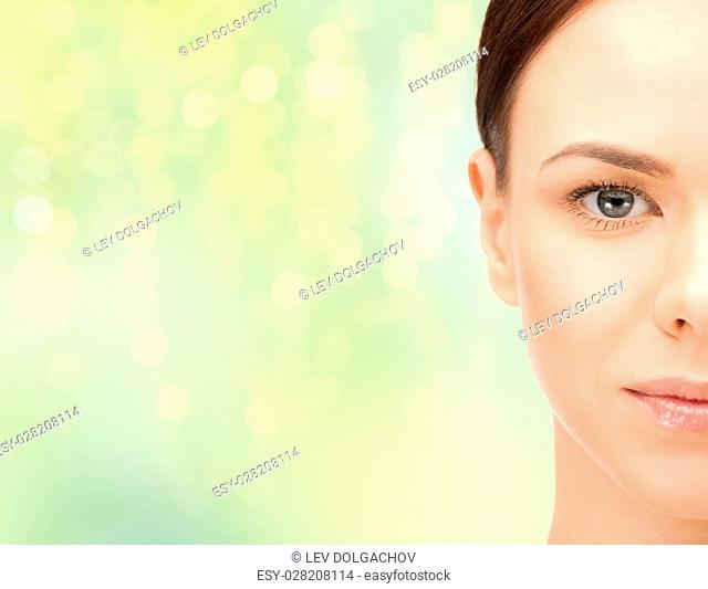beauty, people and health concept - beautiful young woman half face over green lights background