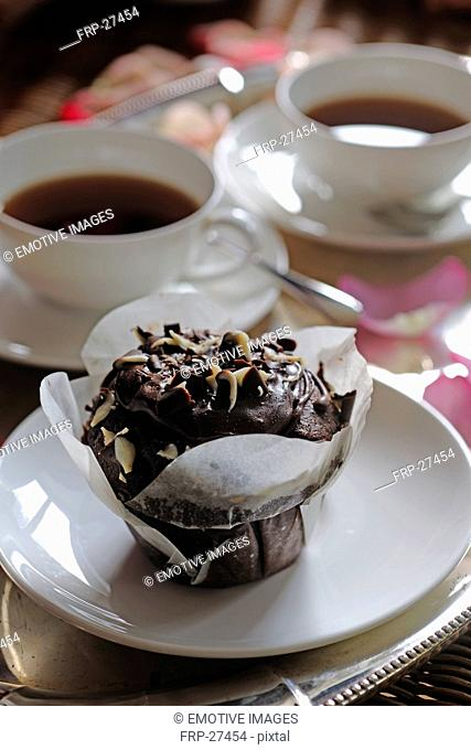 Small chocolate cake and two cups of coffee
