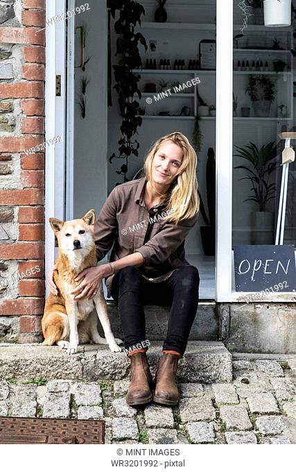 Smiling female owner of plant shop sitting on steps outside her store, a dog sitting next to her