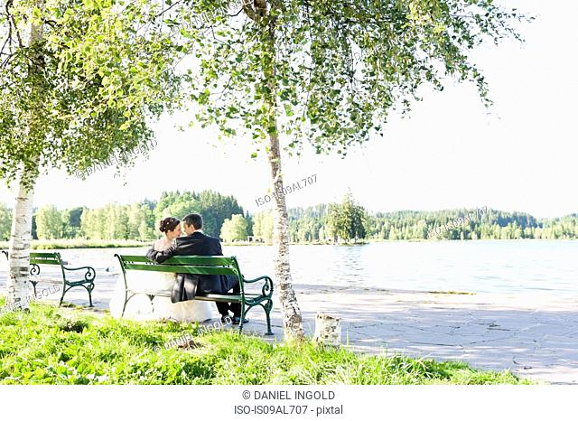 Rear view of bride and bridegroom sitting on riverside park bench