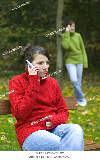 Two teenagers, twin sisters, calling with mobile phones