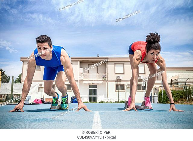 Young male and female sprinters on their marks on running track