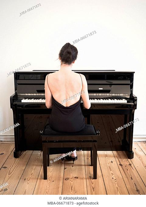 Rear view of a woman in a black dress playing on a black digital piano