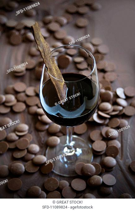 A glass of red wine with a piece of broken dark chocolate