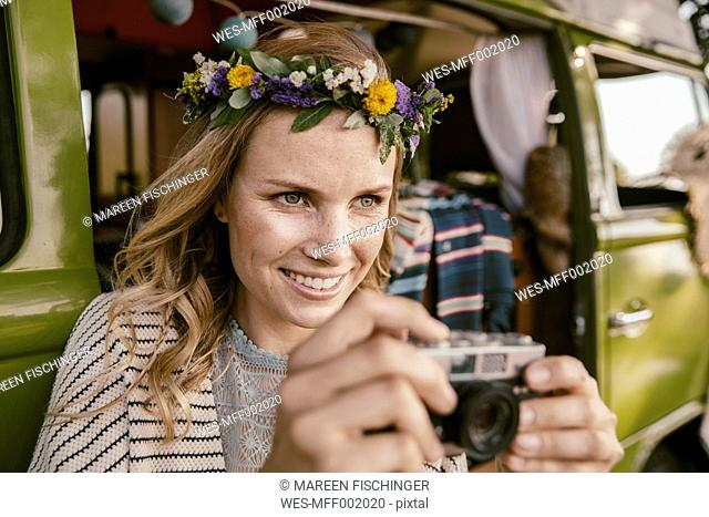 Hippie woman with analog camera in front of van