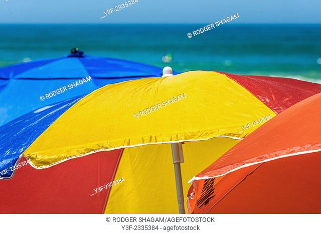Colourful beach umbrellas provide protection (shade) from the harsh sun and the colours brighten the beach. Cape Town, South Africa