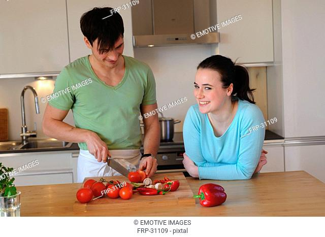 Young couple in kitchen slicing vegetables