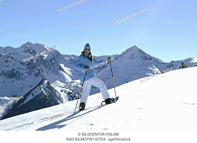 woman in winter hiking with snow shoes