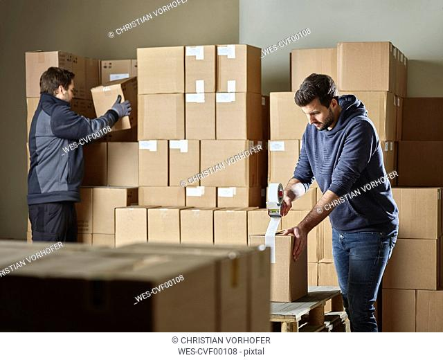 Workers closing packages with package tape