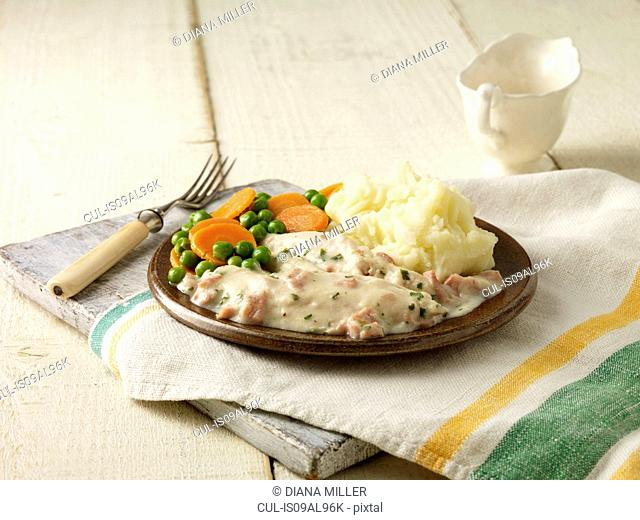 Plate of chicken breast fillets in cheese and bacon sauce with peas, carrots and mashed potatoes