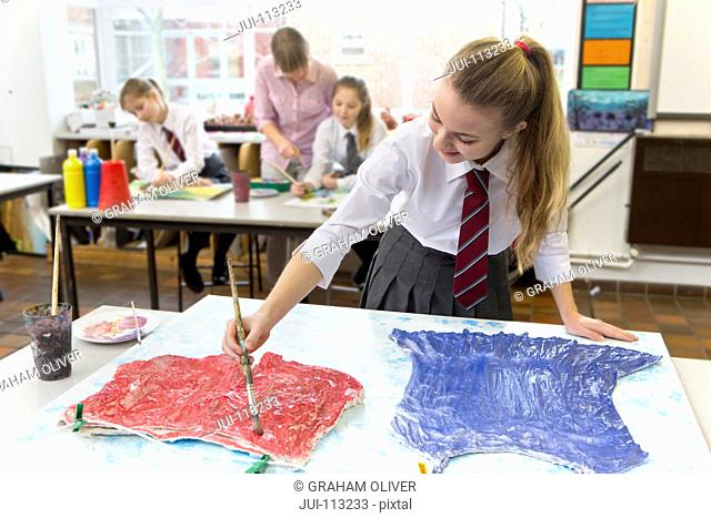 Middle school student painting clothing on canvas in art class