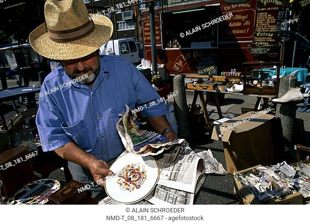 Mature man holding a ceramic plate, Bermondsey Market, Bermondsey, London, England