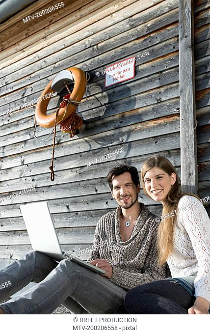 portrait young couple sitting wooden wall laptop