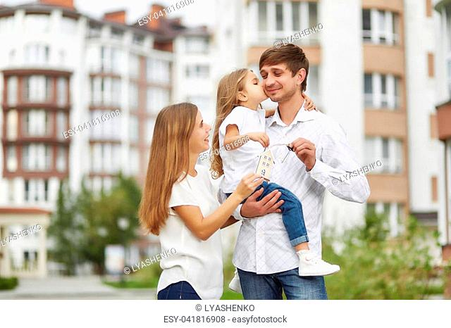 Shot of a happy young family posing together in front of new apartment building. Little girl kissing her father.Young woman posing with her daughter and husband...