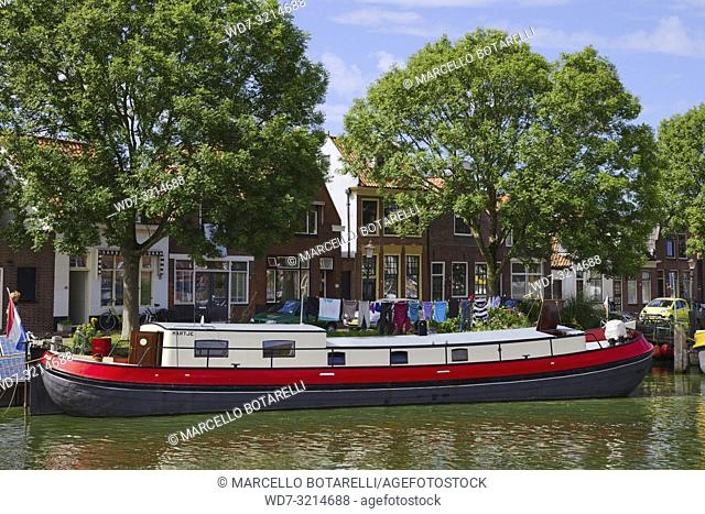 House boat in Enkhuizen, small city of northern Holland, boat transformed into home, behind traditional houses