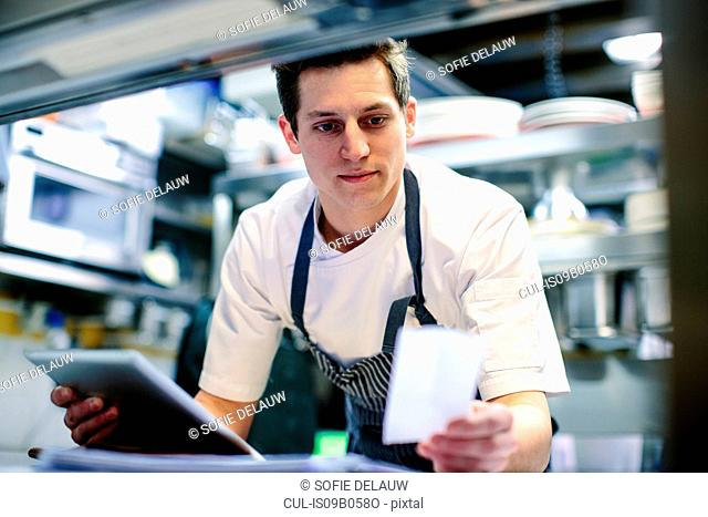 Young male chef using digital tablet and reading food order in kitchen